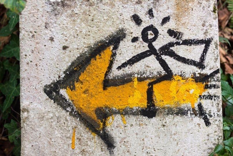 Freccia gialla con pellegrino disegnato a cavalcioni