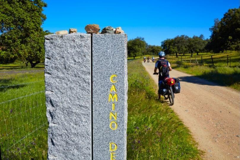 Pellegrino in bici vicino a pilastro che indica il cammino di santiago