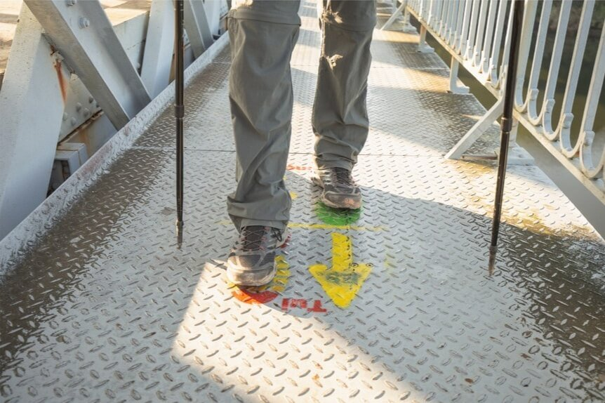 Pellegrino su un ponte in ferro sul cammino portoghese