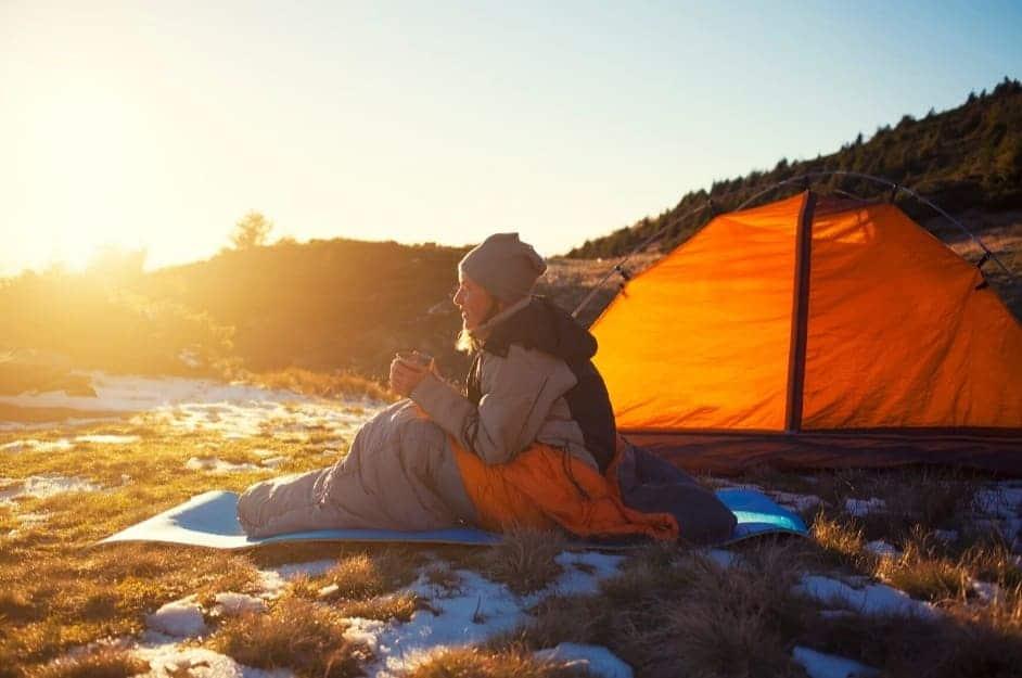 Ragazza in tenda si sveglia al mattino presto