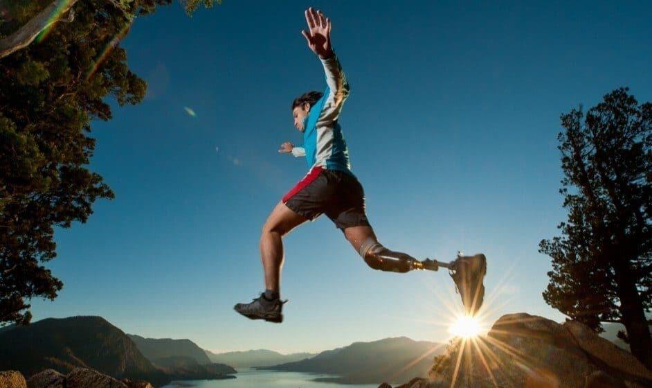 Ragazzo con protesi alla gamba salta al tramonto