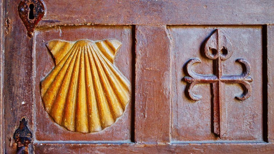 Simboli cammino di santiago intagliati su una porta