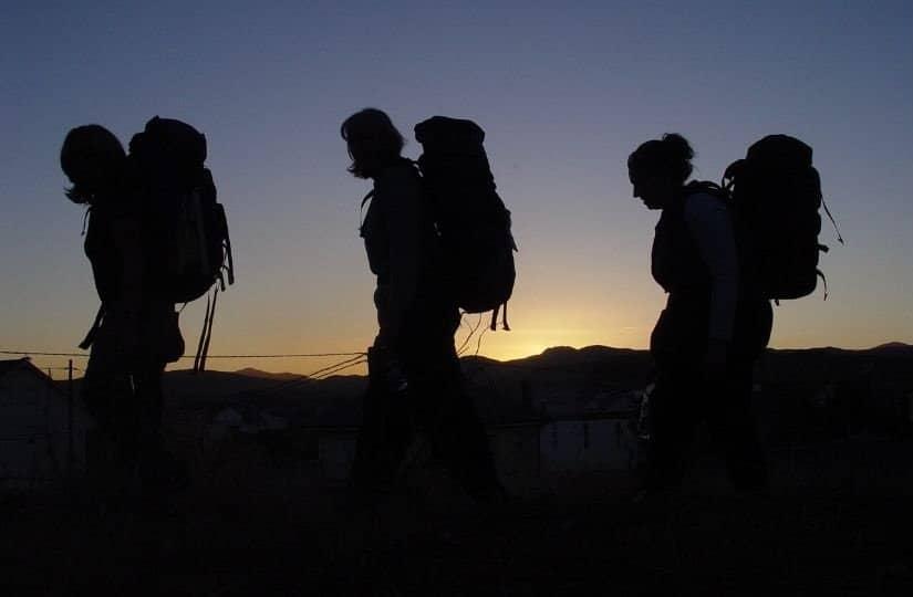 Tre pellegrine camminano al calar del sole