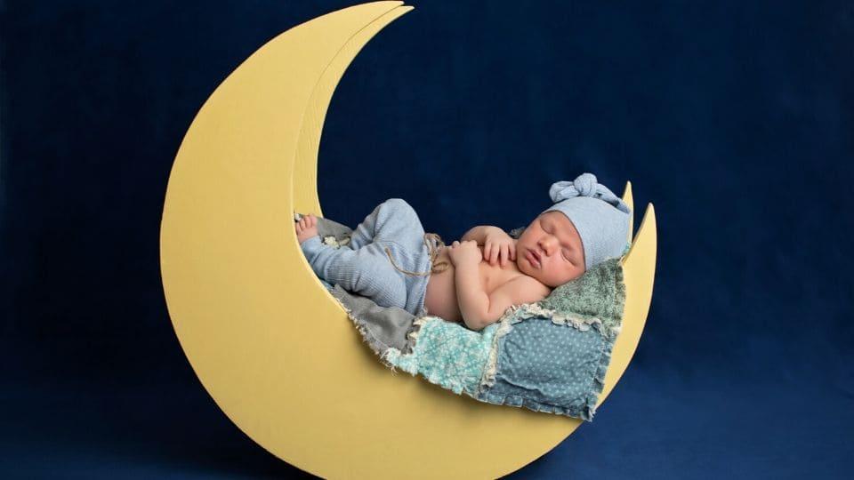 Un bambino piccolo dorme su una mezza luna in legno