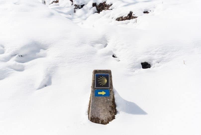 Un mojon del cammino di santiago tra la neve