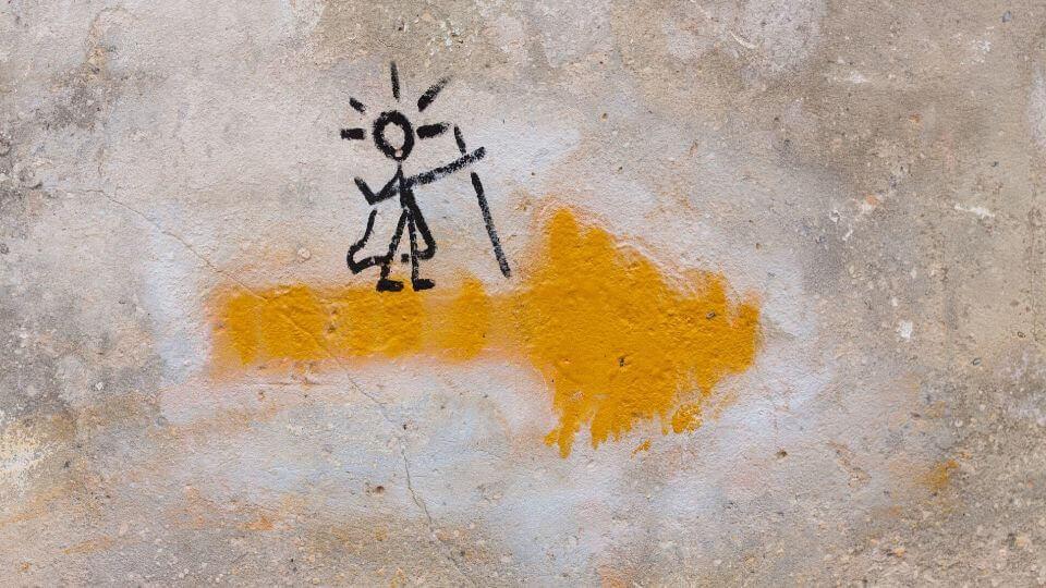 Una freccia gialla con pellegrino disegnato sopra