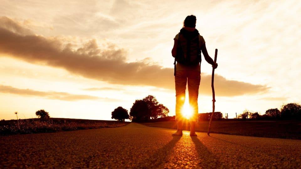 Una pellegrina cammina a piedi scalzi al tramonto