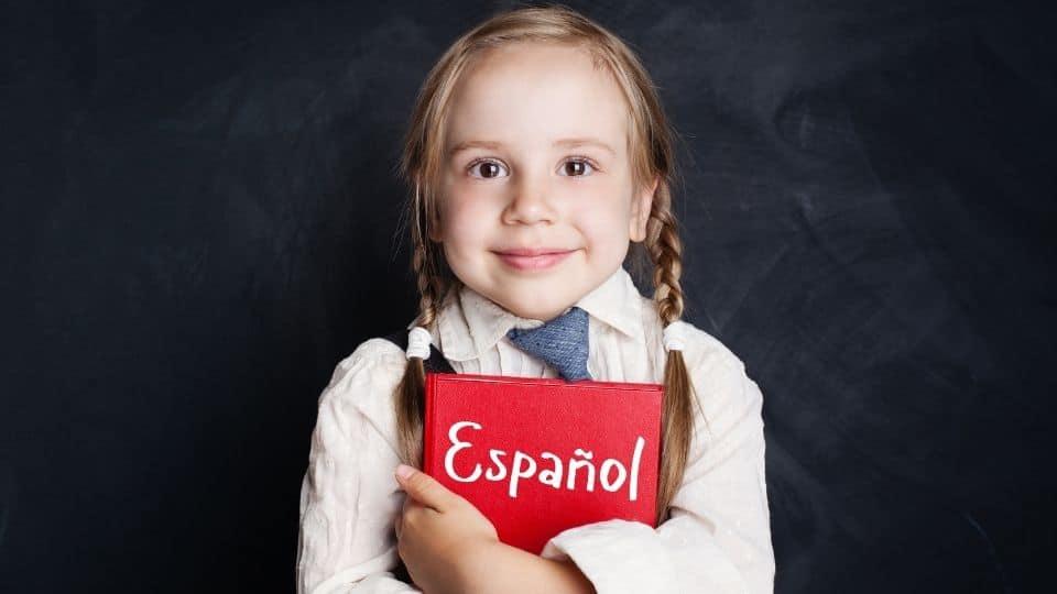 Bambina ha tra le braccia un libro di spagnolo
